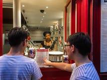 Men customers choose menu item at crepe stand in Paris Royalty Free Stock Photography