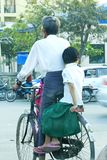 Men cycling with girls in Myanmar royalty free stock image
