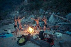 Men dancing around fire on beach