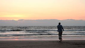 Men dancing on the beach. Men dancing on the beach in sunset rays stock video