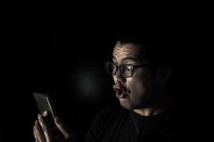 Men in the dark facial expression lust while browsing smartphones Stock Photography