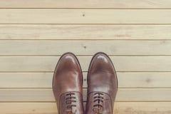 Men& de cuero marrón clásico x27; zapatos de s en fondo de madera Fotos de archivo