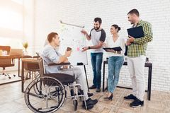 Office workers and man in a wheelchair discussing business moments while working in a modern office. Royalty Free Stock Images
