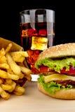 Menü des Cheeseburgers, Pommes-Frites, Glas Kolabaum auf hölzernem Schreibtisch auf Schwarzem Lizenzfreie Stockfotos