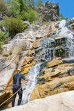 Men descending waterfall Stock Photo