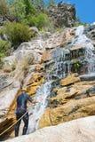 Men descending waterfall. Youn man descending waterfall in rappelling Stock Photo