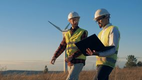 Men discuss a project while checking wind turbines in the field. Environmental energy concept.