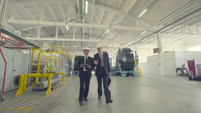 Men discussing business on factory. Two businessmen walking through factory and discussing case stock video footage