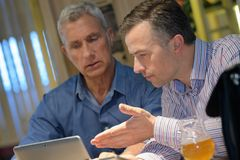Men discussing information on tablet screen stock photos