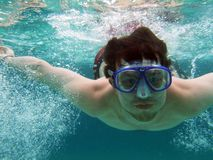 Men dive with bubbles. Young men dive in blue sea with a lot of bubbles Stock Image