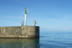 Men do fishing from the pier in Ravine Saint-Gilles De Reunion, France. Royalty Free Stock Photo