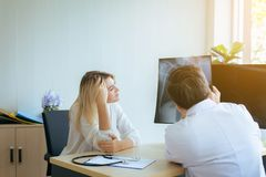 Man doctor examining X-ray results to woman patient,Infertility counseling and suggestion using new technology. Men doctor examining X-ray results to women royalty free stock photography