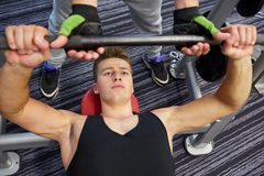 Men doing barbell bench press in gym. Sport, fitness, equipment, lifestyle and people concept - man doing barbell bench press in gym with personal trainer or royalty free stock images