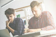 Men doing paperwork in office. Portrait of two handsome caucasian males doing paperwork and using smartphone in modern office. Team work concept Stock Image