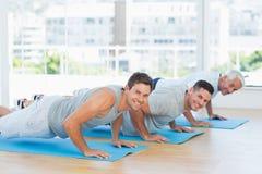 Men doing push ups on exercise mats royalty free stock photos