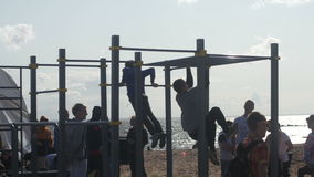 Men doing strength exercises on a pull-up gym at. Men doing strength exercises on pull-up gym at the beach. VK Fest Saint Petersburg 18 july 2015 stock video footage
