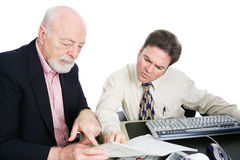 Men Doing Taxes. Senior men going over his taxes with an accountant.  White background Stock Photography