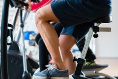 Men doing workout on exercise bike at gym. Group of men doing workout on exercise bike at gym royalty free stock images