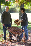 Men doing yard work in autumn Stock Images