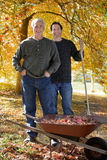 Men doing yard work together in autumn Royalty Free Stock Photos