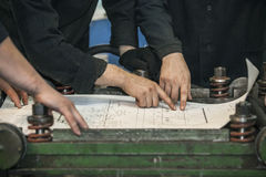 Men with drawings working in an old factory to install the equip stock images