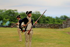 Men dressed as soldiers,reenacting musket use,Fort Ticonderoga,New York,2014 Royalty Free Stock Photo