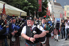 Men dressed in kilts playing Scottish pipes Stock Images