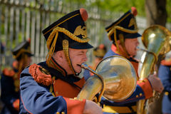 A men dressed in an old military uniform playing the trumpet in Royalty Free Stock Images