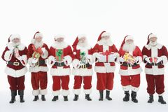 Men Dressed Santa Claus Outfits Standing With Gifts. Men dressed in Santa Claus outfits standing with gifts isolated over white background Stock Image