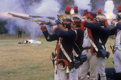Men dressed in 18th century American military costume fire muskets during a Revolutionary War battle reenactment held in New Winds Royalty Free Stock Photo