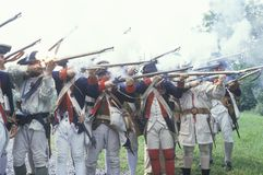 Men dressed in 18th century American military infantry costume fire muskets during reenactment of American Revolutionary War Royalty Free Stock Images