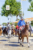 Men dressed in traditional costumes riding horses and celebrating Seville`s April Fair. Stock Photos