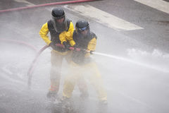 Men dressed in yellow firemen slickers Stock Photo