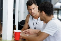 Men drinking beer after exercising stock image