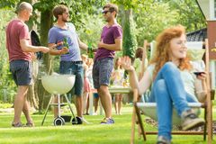 Men drinking beer and grilling. Girl sitting deckchair Royalty Free Stock Images