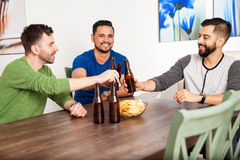 Men drinking beer and making a toast. Group of attractive young men making a toast with beer while hanging out at home Royalty Free Stock Photography