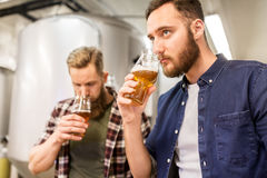 Men drinking and testing craft beer at brewery. Alcohol production, business and people concept - men drinking and testing craft beer at brewery Stock Image