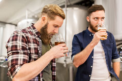 Men drinking and testing craft beer at brewery. Alcohol production, business and people concept - men drinking and testing craft beer at brewery Stock Photos