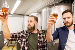 Men drinking and testing craft beer at brewery. Alcohol production, manufacture, business and people concept - men drinking and testing craft beer at brewery Royalty Free Stock Image