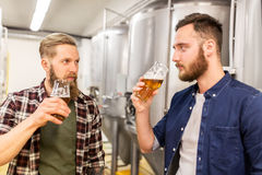 Men drinking and testing craft beer at brewery. Alcohol production, manufacture, business and people concept - men drinking and testing craft beer at brewery Stock Photo