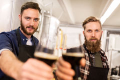 Men drinking and testing craft beer at brewery. Alcohol production, manufacture, business and people concept - men drinking and testing craft beer at brewery Royalty Free Stock Photography