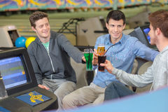 Men with drinks in bowling center Royalty Free Stock Photos
