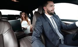 Businessmen with a computer in the car go on a business trip. A men drives a car, and a women uses a laptop and prepares for a presentation Stock Photography