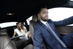Businessmen with a computer in the car go on a business trip. A men drives a car, and a women uses a laptop and prepares for a presentation Royalty Free Stock Image