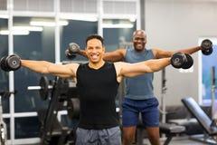 Men dumbbell workout. Fitness men doing dumbbell workout in gym stock image