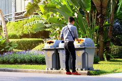 Men are dumping plastic bottles waste into trash bin recycle at sideways walk at garden public stock photography