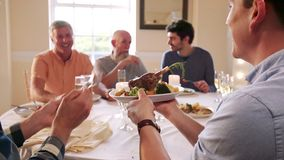 Men Eating At A Dinner Party. Men are eating at a dinner party. One man passes his plate for someone to put a piece of food on it stock video footage