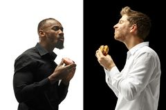 Men eating a hamburger and donut on a black and white background royalty free stock images