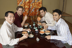 Men Eating Sushi With Chopsticks In Restaurant Stock Photo