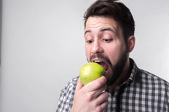 Men eats an apple. bearded guy holding an apple. vegetarian preparing dinner Stock Photo